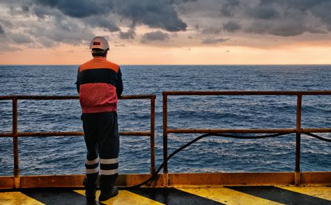 A worker looking out onto the sea from an offshore rig