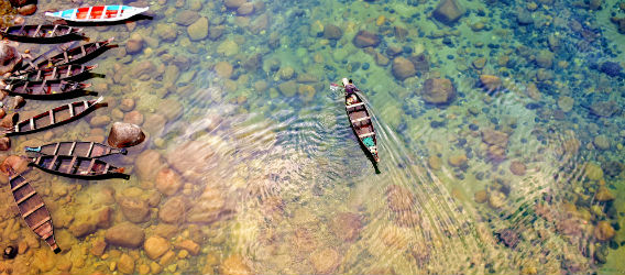 Aerial shot of a boat floating in a river