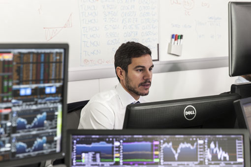 Analyst looking at financial data and graphs on screens