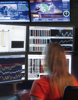 Fixed income and ratings: Analyst looking at several screens displaying graphs