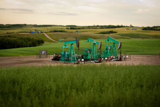 Exploration pump jacks at work in a field in Canada