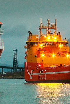 Shot of a lit up red and yellow vessel at sea in Europe