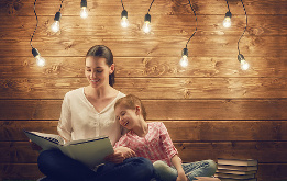 A mother and daughter reading surrounded by lightbulbs