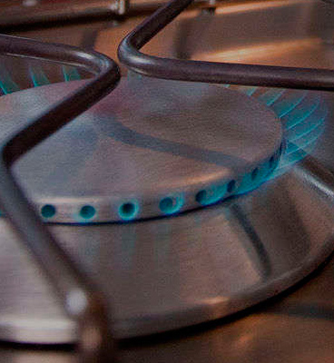 Close-up of a butane gas-powered kitchen stove burner.