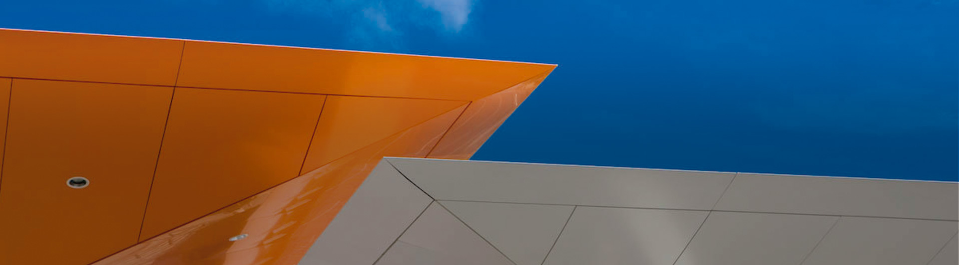 Close-up of an orange and a gray inside out umbrella shaped canopy at a Repsol service station