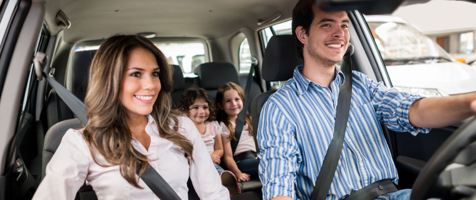 Automotive industry. A safe family in a safe car, all of them wearing their safety belts.