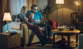 Family looking at a laptop in the living room with the lamp switched on: Repsol electricity and natural gas.