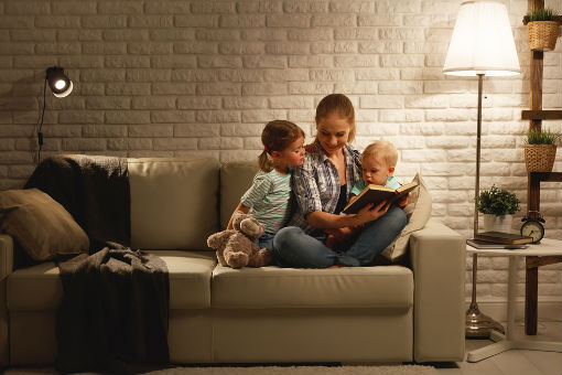 A mother reads a book with her children by the light of a lamp.