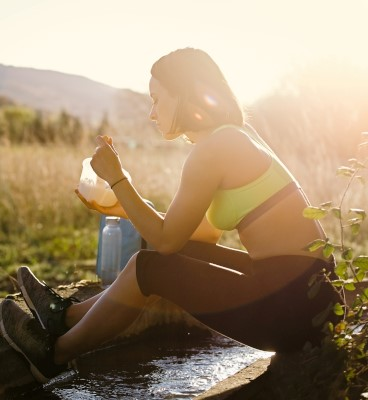 A girl eats a snack while on a hike in the country. Chemicals.
