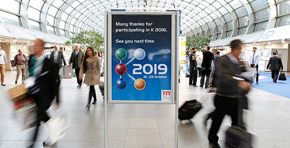 Picture of a K 2019 promotional event poster in a hall filled with many people.