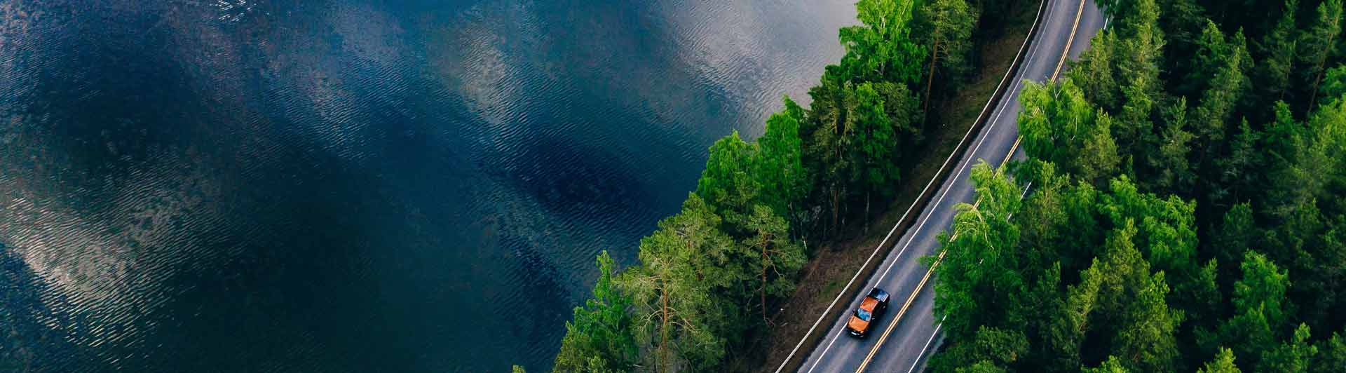 Birdseye view of a highway along a forest and lake