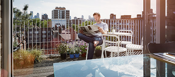 A man reading the newspaper on a rooftop terrace in broad daylight