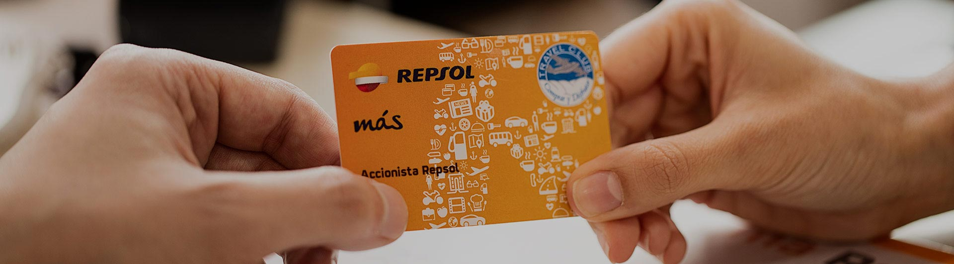 Two hands holding a Repsol Más card