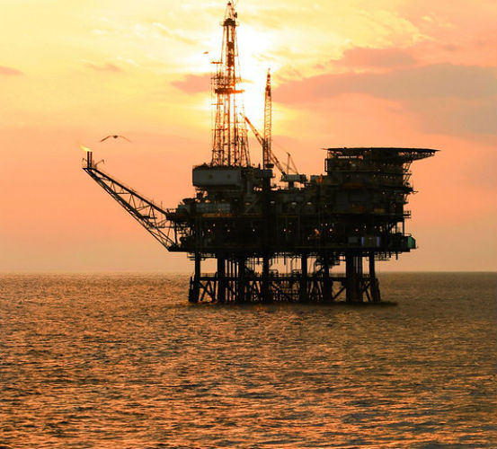 Oil platform in the ocean at sunset
