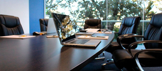 A meeting room table with a laptop on it