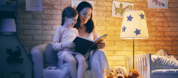 Mother daughter reading a book by a lamp