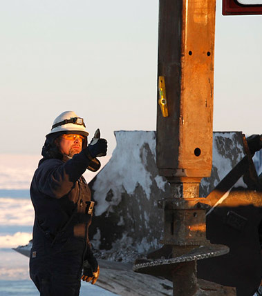 An operator working on a ship in the icy waters giving the 'thumbs up'