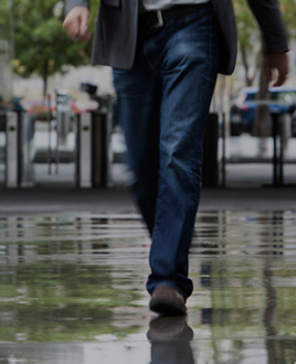 A man's legs walking into Campus on a wet floor. Advisory Committee