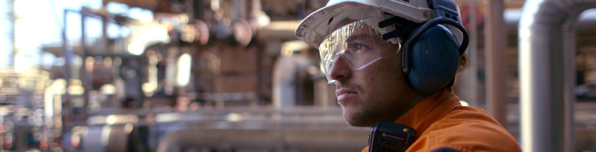 A worker at a refinery wearing safety gear and other elements.