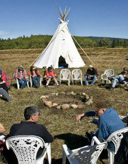 A group of people sitting around an indigenous teepee