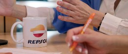 Close-up of a Repsol coffee cup on a meeting table