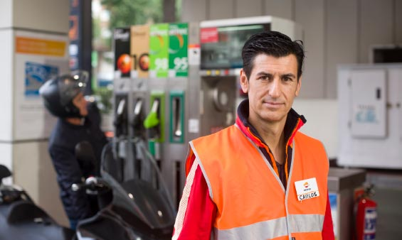 A Repsol employee standing by gas pumps at a service station