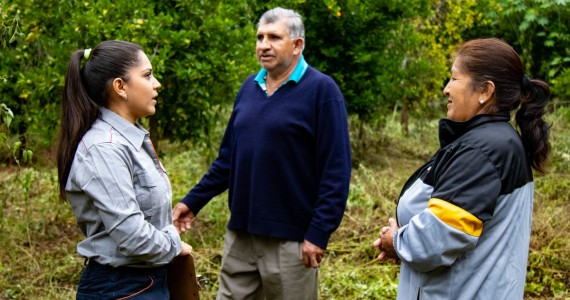 Repsol employee talks with two people from a Bolivian community