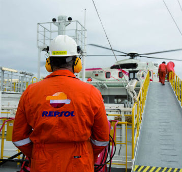A Repsol operator wearing safety gear and observing a helicopter