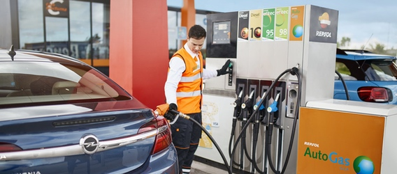A Repsol service station employee refilling a car with gas
