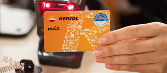 A hand swiping a Repsol Más card through a dataphone.