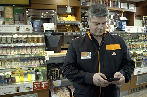 An employee inside a Repsol service station using his mobile phone.