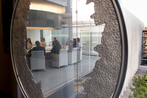 A scene during an important meeting at Repsol Campus, as seen though a strange hole in the building.