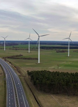 Aerial view of four windmills along a highway with no traffic.