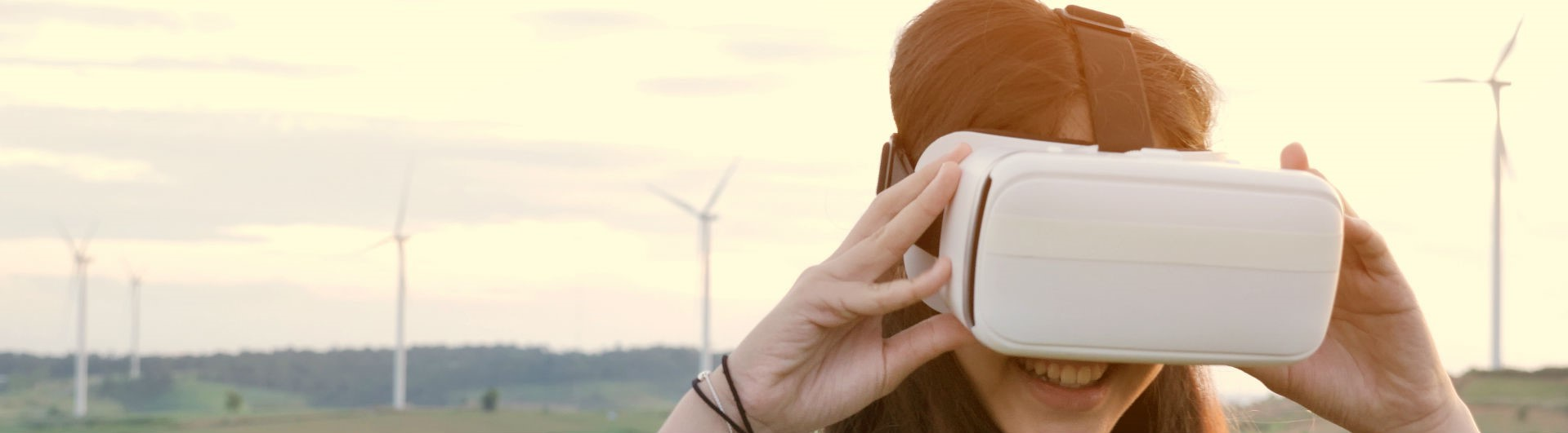A young girl using a VR headset at a wind farm