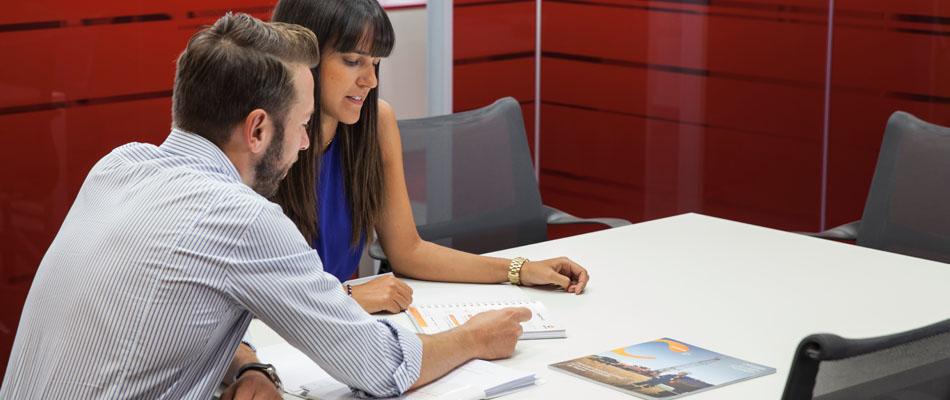 Comprometidos con nuestros empleados. Dos empleados sentados en una mesa examinando documentación formativa